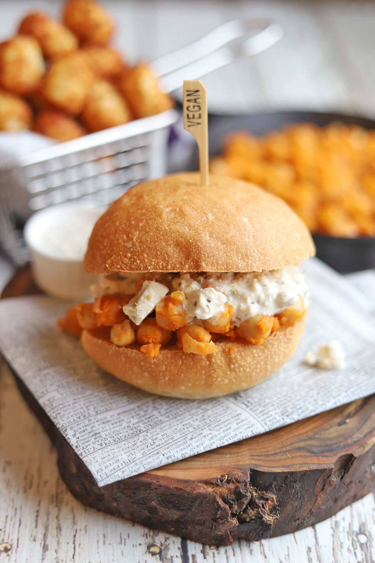 Chickpea sandwich on table with tater tots.