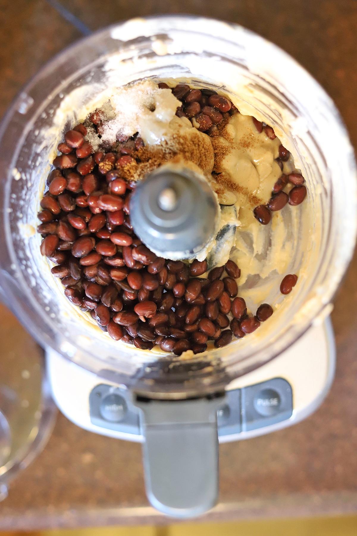 Black beans, cumin, tahini, and lemon juice in food processor.