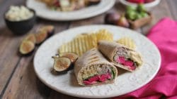 Double hummus wrap on plate with figs.