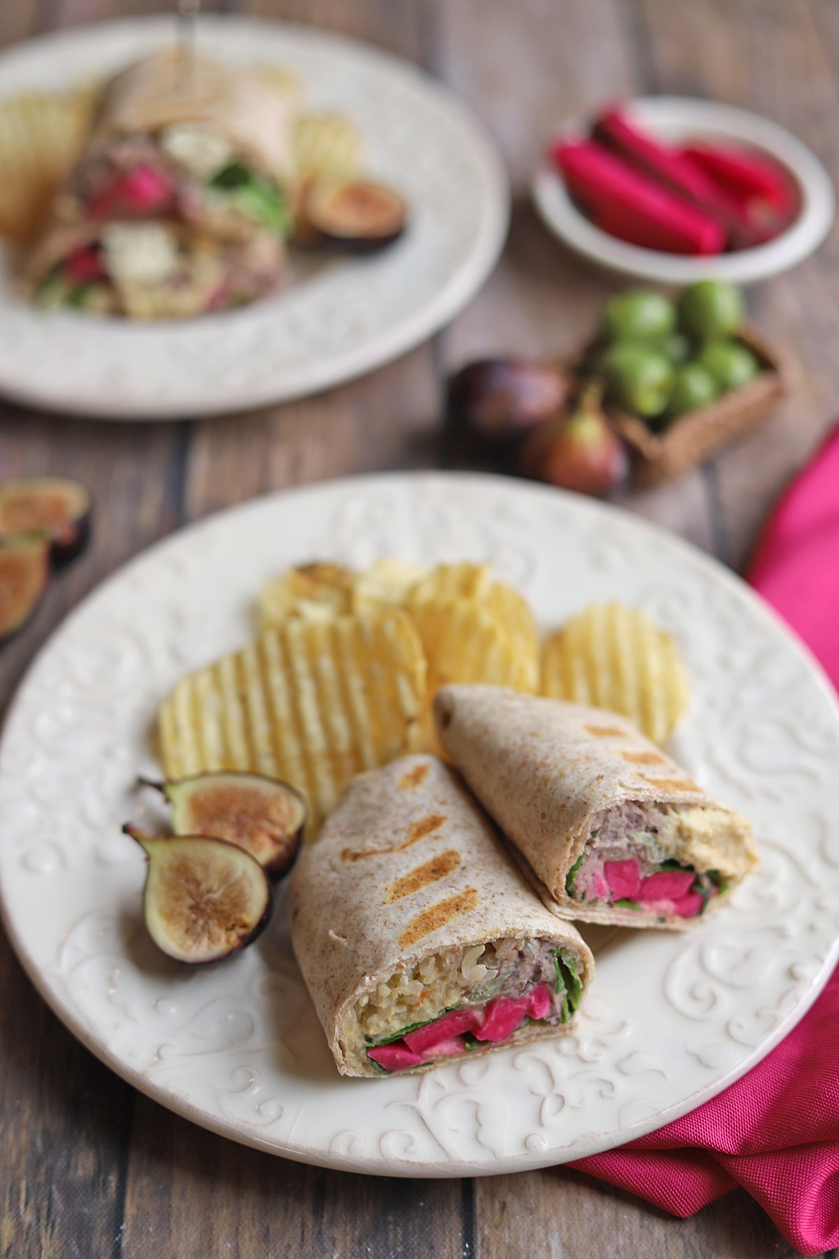 Wraps on plates with potato chips.