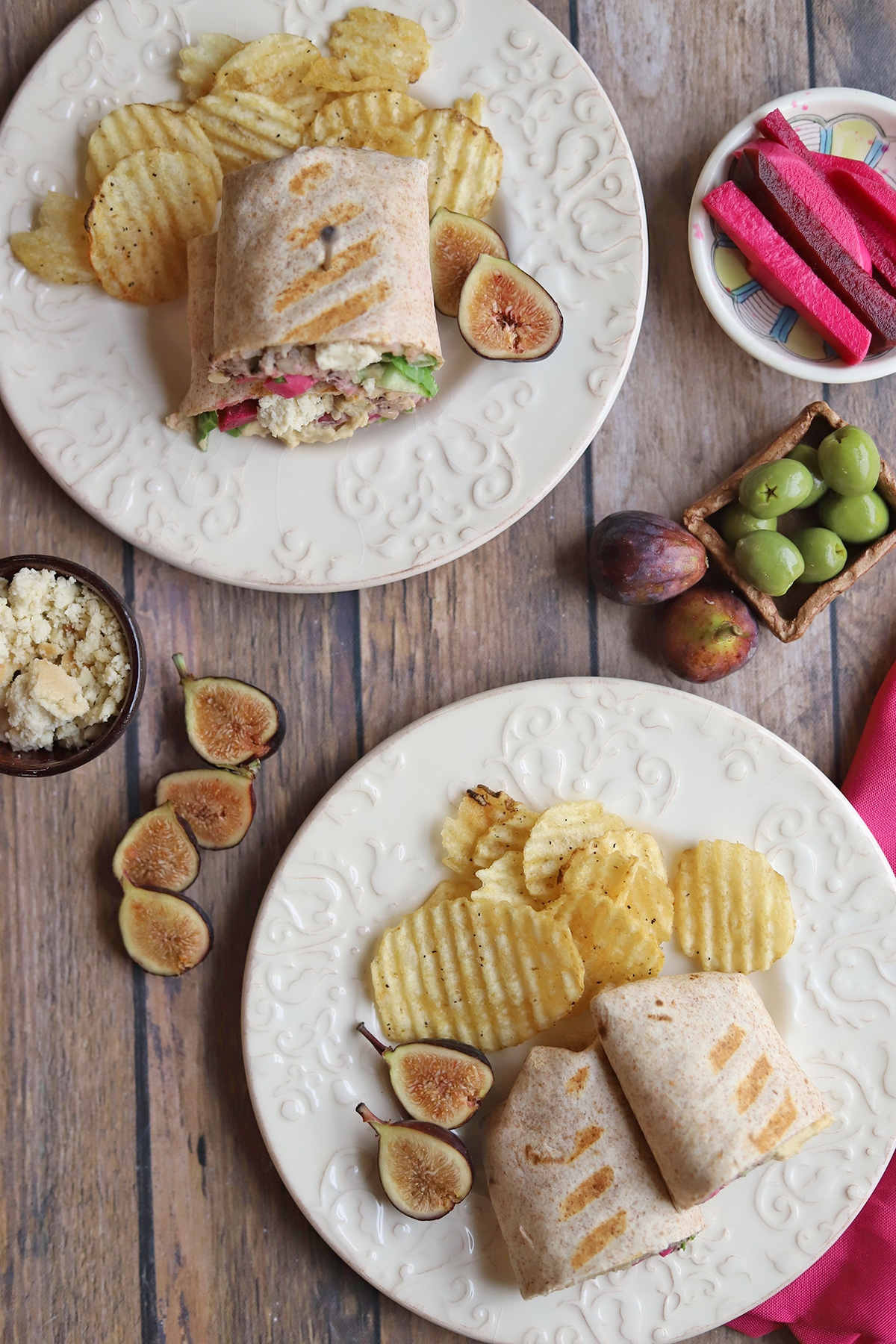 Overhead plates with wraps and potato chips on table.