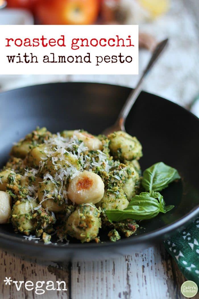"Roasted gnocchi with almond pesto in bowl. Plus text, ""roasted gnocchi with almond pesto"" and ""vegan."""