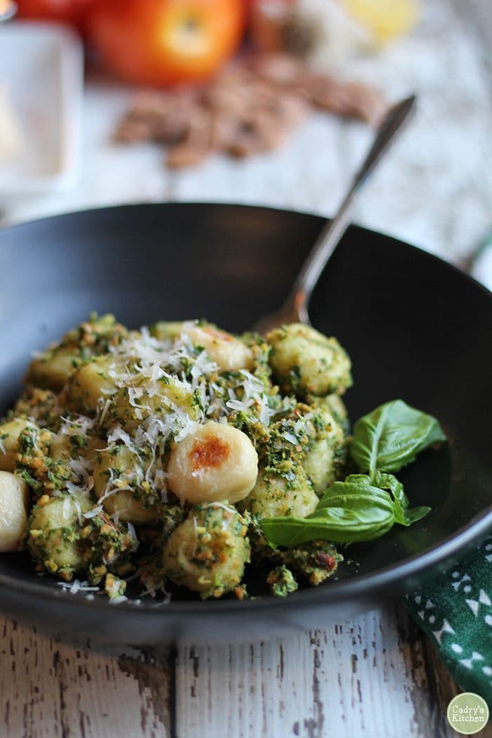 Roasted gnocchi with almond pesto in black bowl.