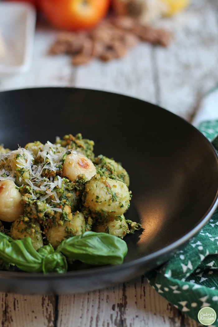 Roasted gnocchi with vegan almond pesto in bowl with basil.