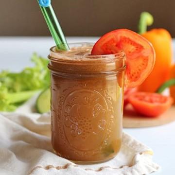 Glass of juice with tomato slice & straw.
