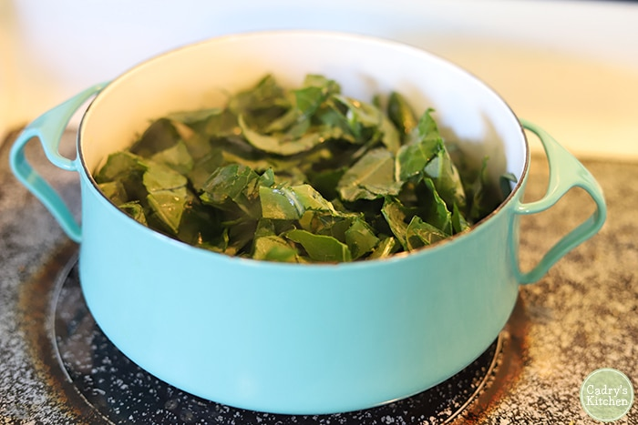 Collard greens in a teal soup pot.