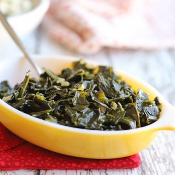 Collard greens in a yellow Pyrex on a table.
