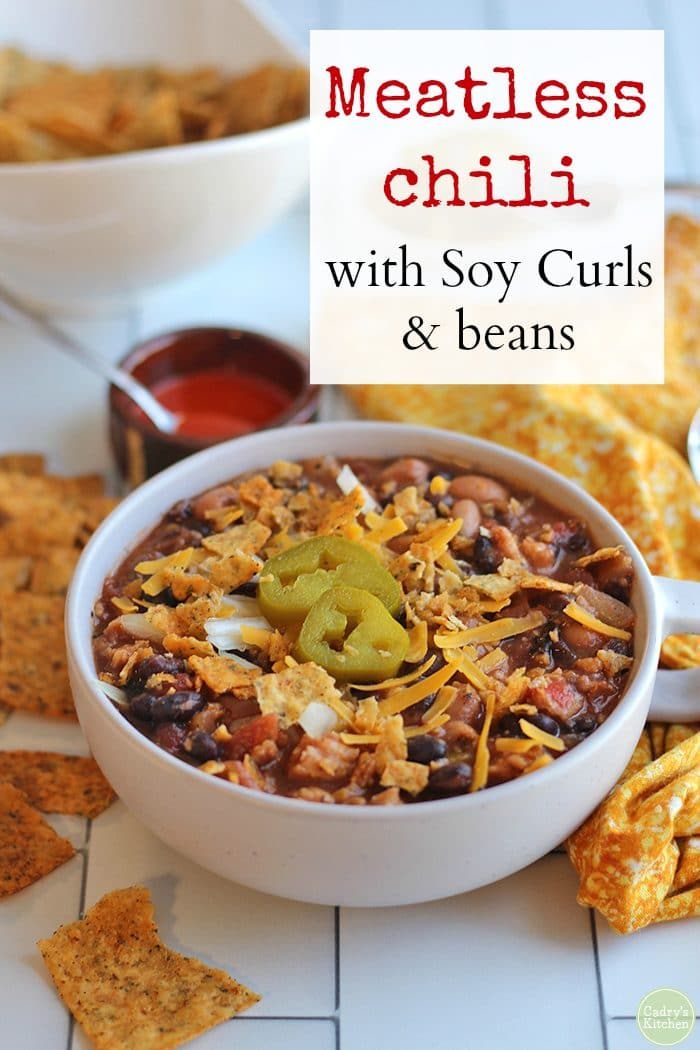 Text: Meatless chili with Soy Curls and beans. Bowl of chili topped with non-dairy cheese, jalapeno pepper slices, and crushed taco chips.