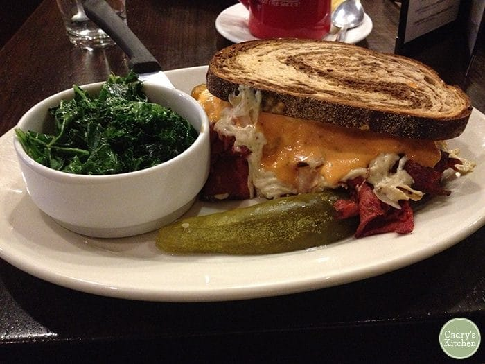 Seitan reuben on plate with pickle spear and sauteed kale.