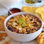 Meatless chili with non-dairy cheese and tortilla chips in bowl.