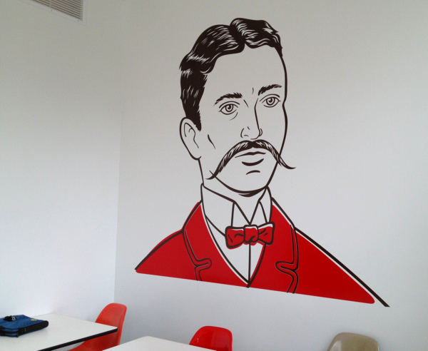 Painted portrait of man with long moustache on wall at Upton's Breakroom.