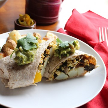 Breakfast burrito on plate by red napkin.