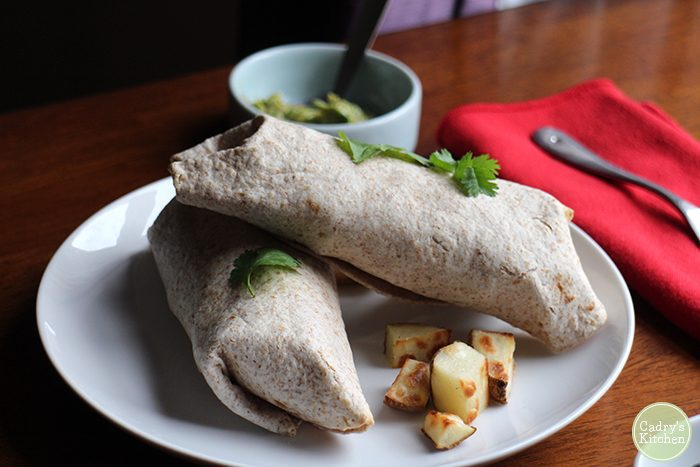 Two burritos stacked on top of each other with cilantro and roasted potatoes.