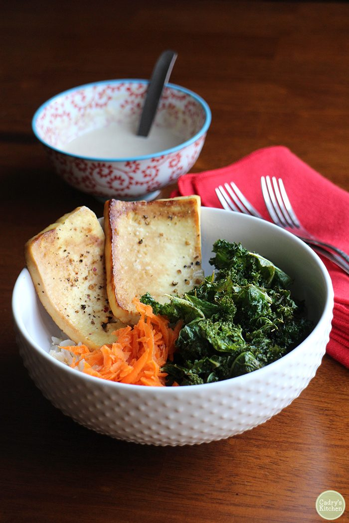 White bowl with tofu, kale chips, and shredded carrot on rice. Tahini sauce in background.