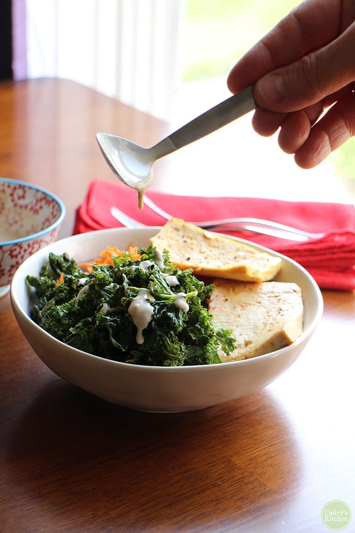 Spoon dripping with tahini sauce over kale chips, tofu slabs, and brown rice in bowl.