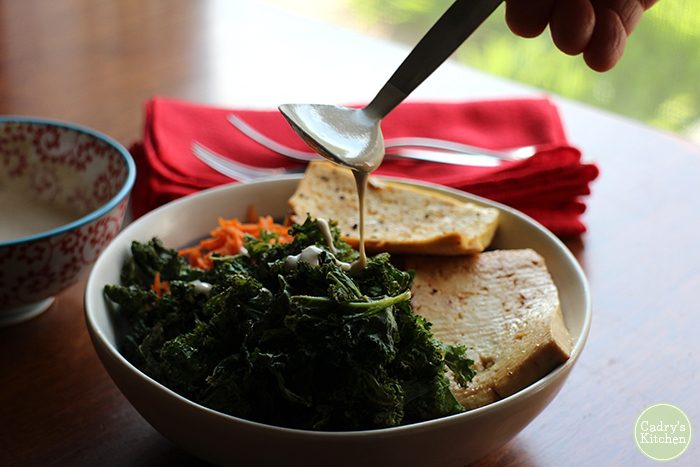 Spoon drizzling tahini sauce onto kale chips, tofu slabs, and carrots in bowl.