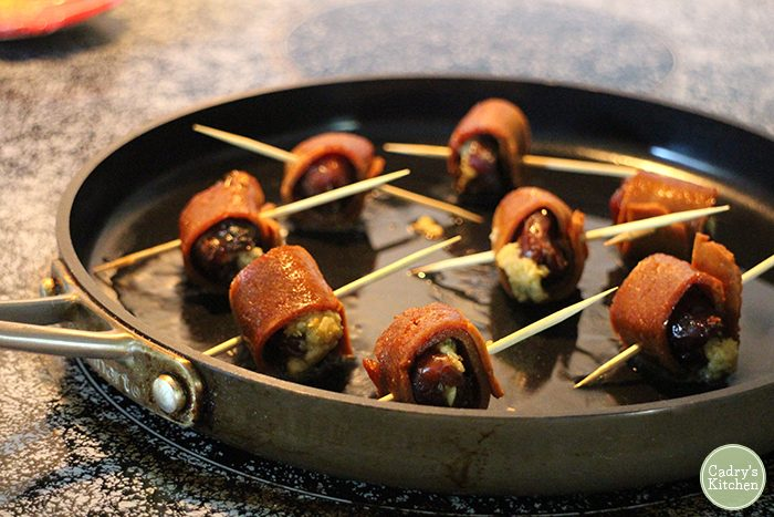 Bacon wrapped dates speared with toothpicks frying in skillet.