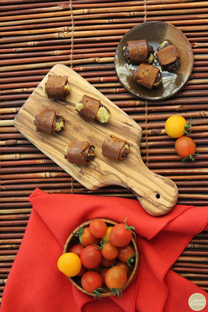 Overhead cutting board & plates with bacon wrapped dates. Small bowl of cherry tomatoes.