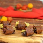 Cashew cheese stuffed dates that are wrapped in seitan bacon on cutting board.