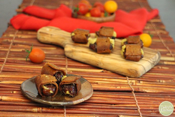 Vegan bacon wrapped dates with cashew cheese on little plate by cutting board & red napkin.