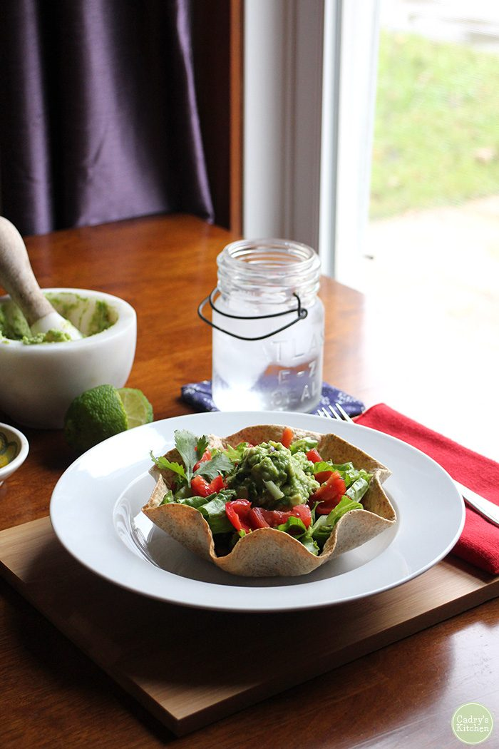 Crisp tortilla bowl with salad on table by guacamole and water.