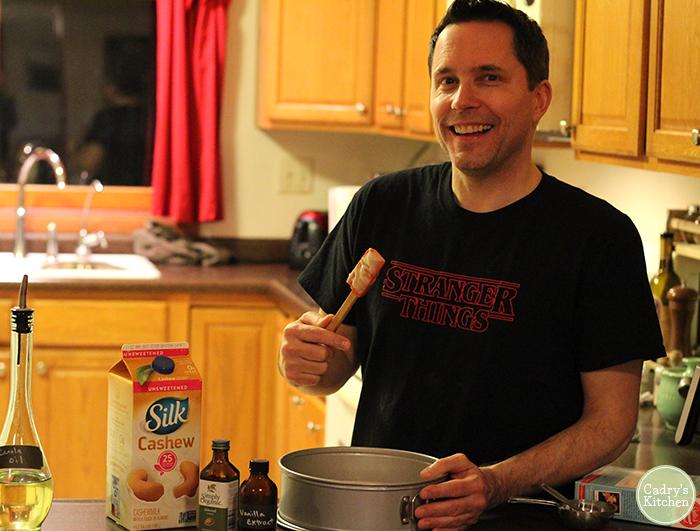 David holding spatula over cake pan.