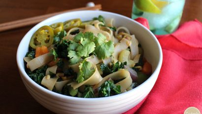 Noodle stir fry in white bowl with cilantro and jalapeno peppers.