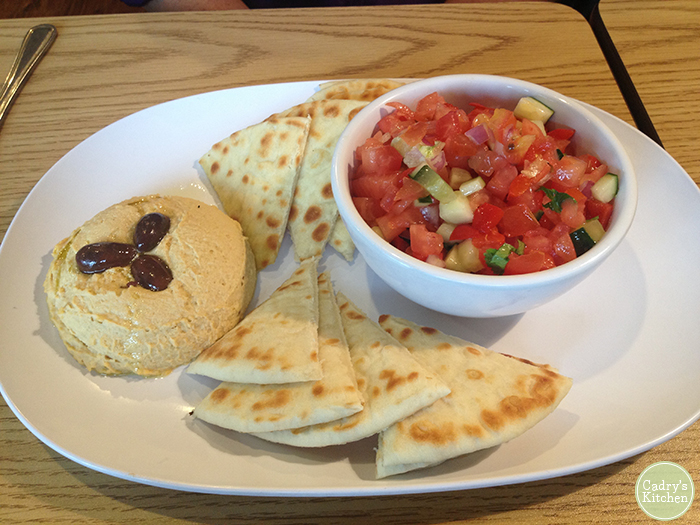 Hummus and pita bread on plate with tomato cucumber salad. It's a vegan Quad Cities option.