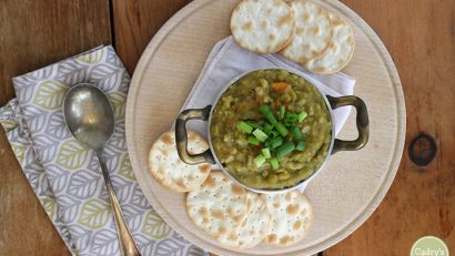 Overhead view of vegan split pea soup in small pot with crackers and spoon.