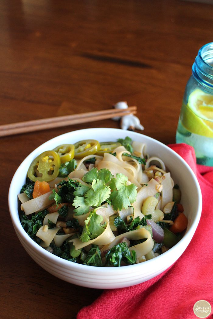 Rice noodles with kale and bell peppers in bowl by chopsticks and water.
