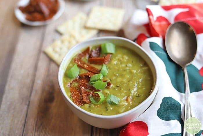 Vegan split pea soup in bowl with spoon & napkin.