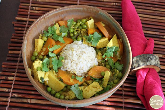 Curry with tofu, carrots, and peas in bowl with rice.