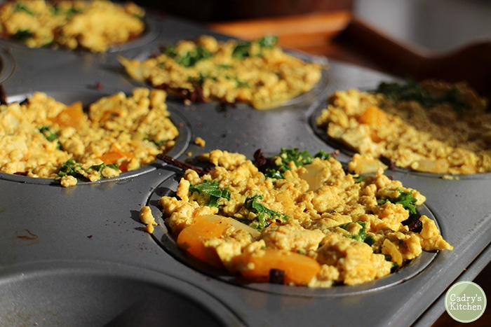 Tofu scramble over grated potato in muffin cups for breakfast nests.