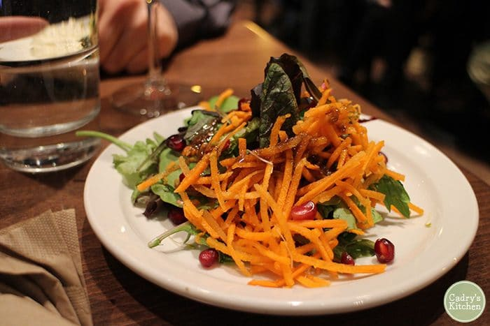 Salad on plate with pomegranate tendrils.