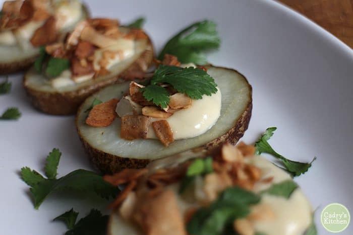 Roasted potato slices with cashew cream and coconut bacon on plate.