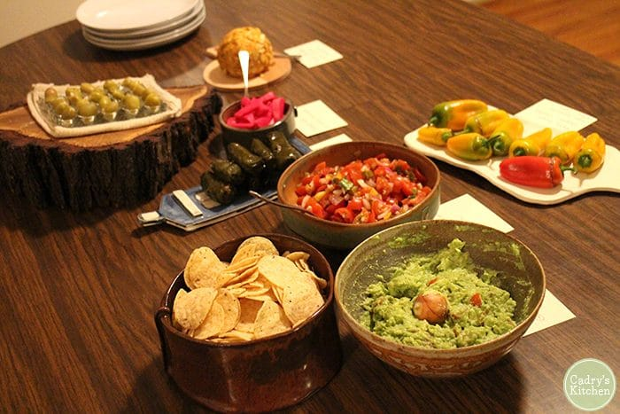 Vegan party appetizers on table - guacamole, salsa, olives, and chips.
