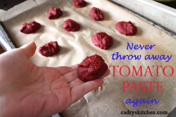 Text overlay: Never throw away tomato paste again. Hand holding frozen tomato paste.