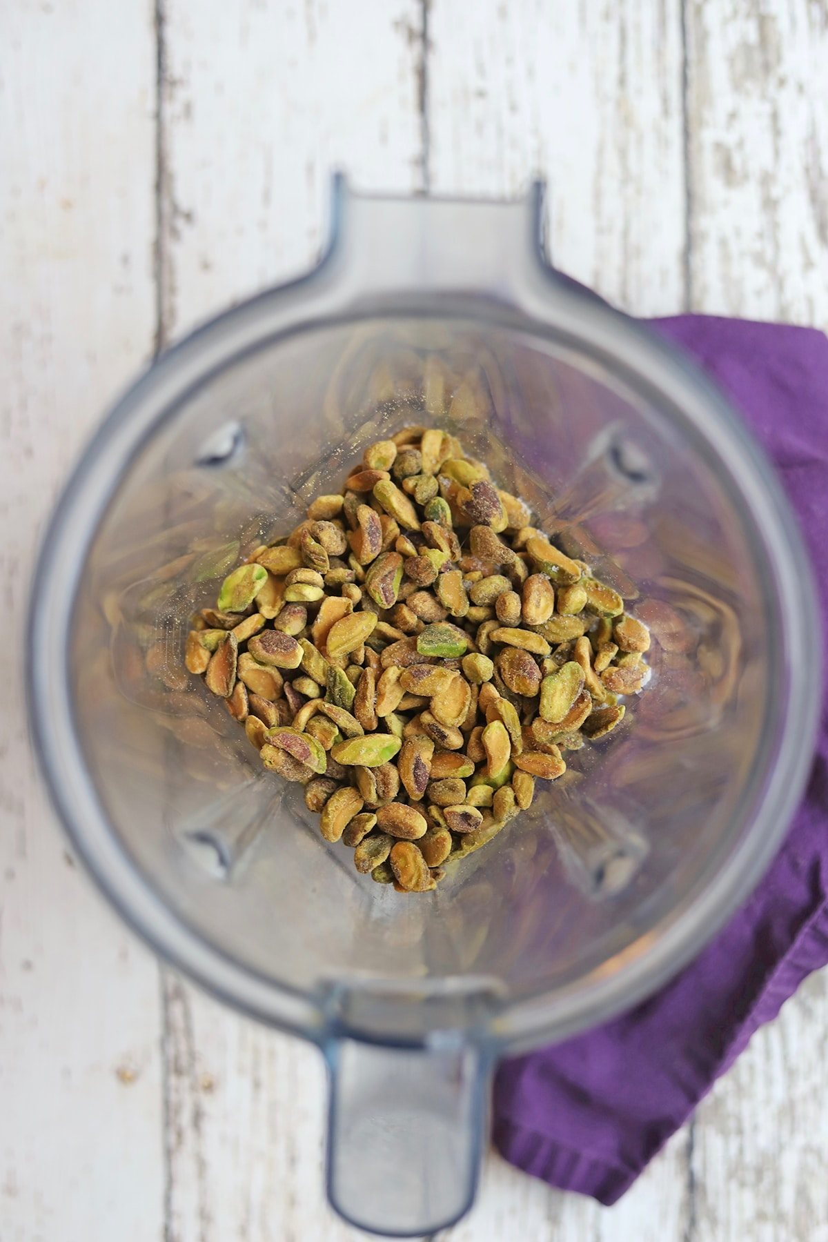 Blender jar with shelled pistachios inside.