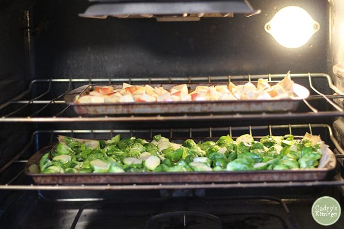 Brussels sprouts and apples roasting on baking sheets in oven.