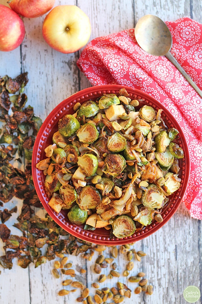 Overhead red bowl with Brussels sprouts, caramelized onions, and apples with red napkin.