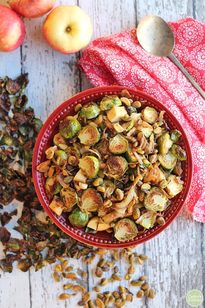 Overhead roasted Brussels sprouts with apples in red bowl by red napkin.