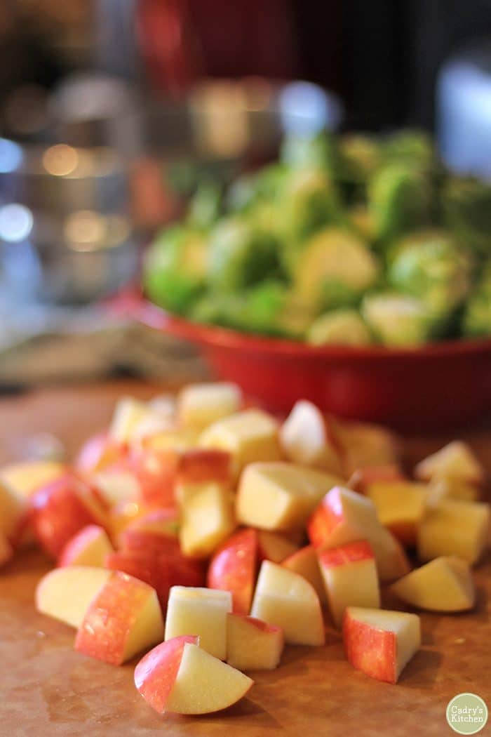 Diced apples on cutting board. Brussels sprouts in red bowl in background.