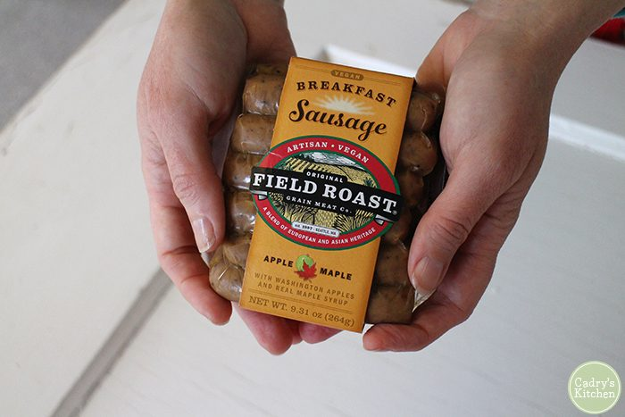 Hands holding a package of Field Roast breakfast sausage.