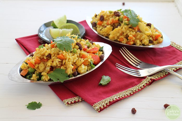 Fried rice on silver platters with lime wedges and forks.
