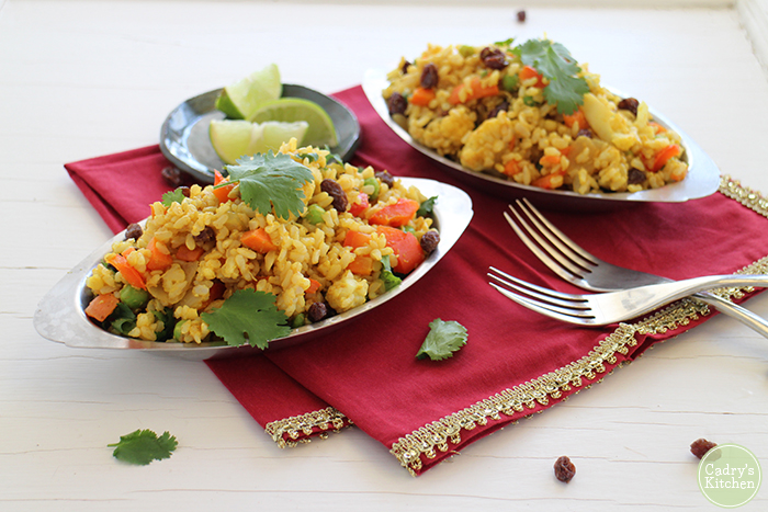 Indian fried rice in stainless steel bowls on red napkin.