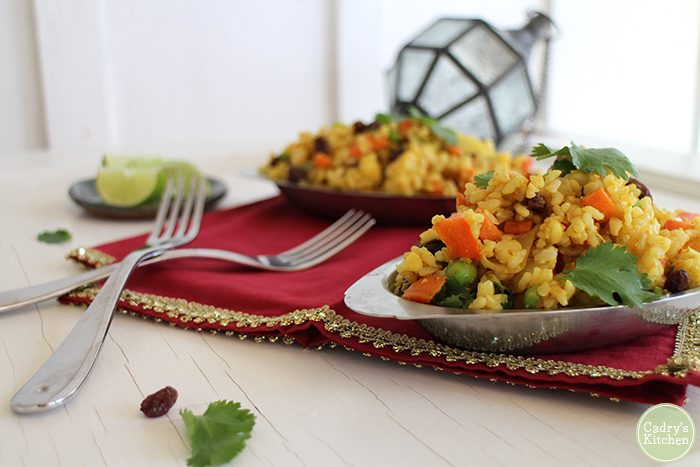 Metal platters with Indian fried rice by forks on red napkins.