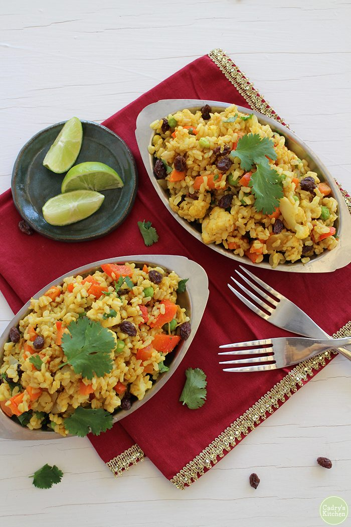 Overhead metal platters with Indian fried rice, forks, and lime wedges on red napkin.