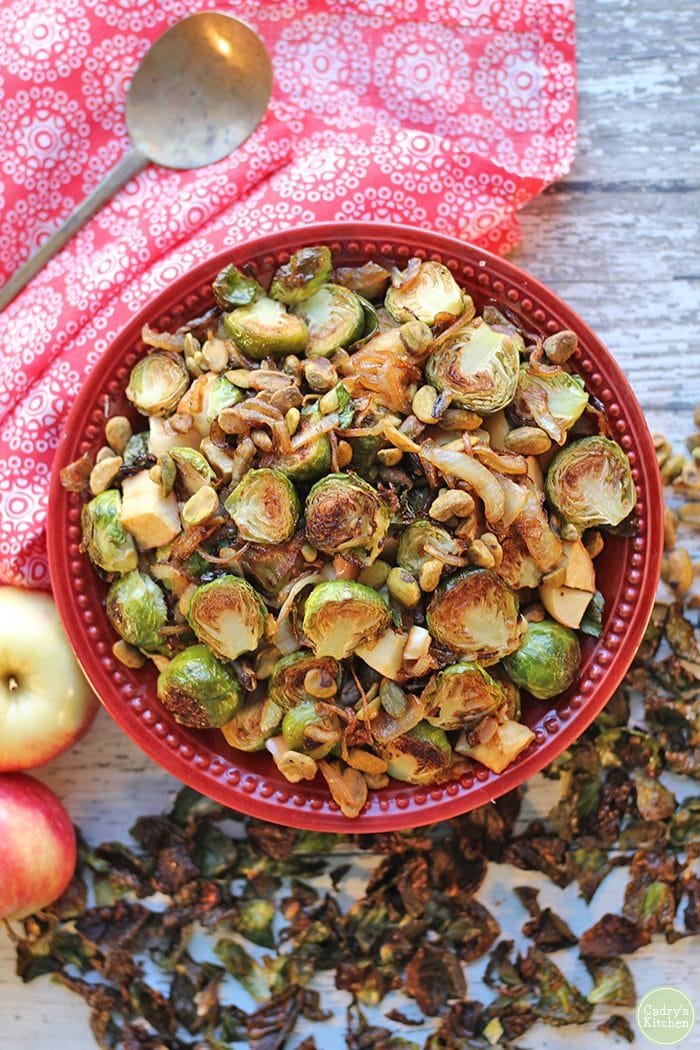 Overhead roasted Brussels sprouts with apples, caramelized onions, and pistachios. Red napkin on white table.