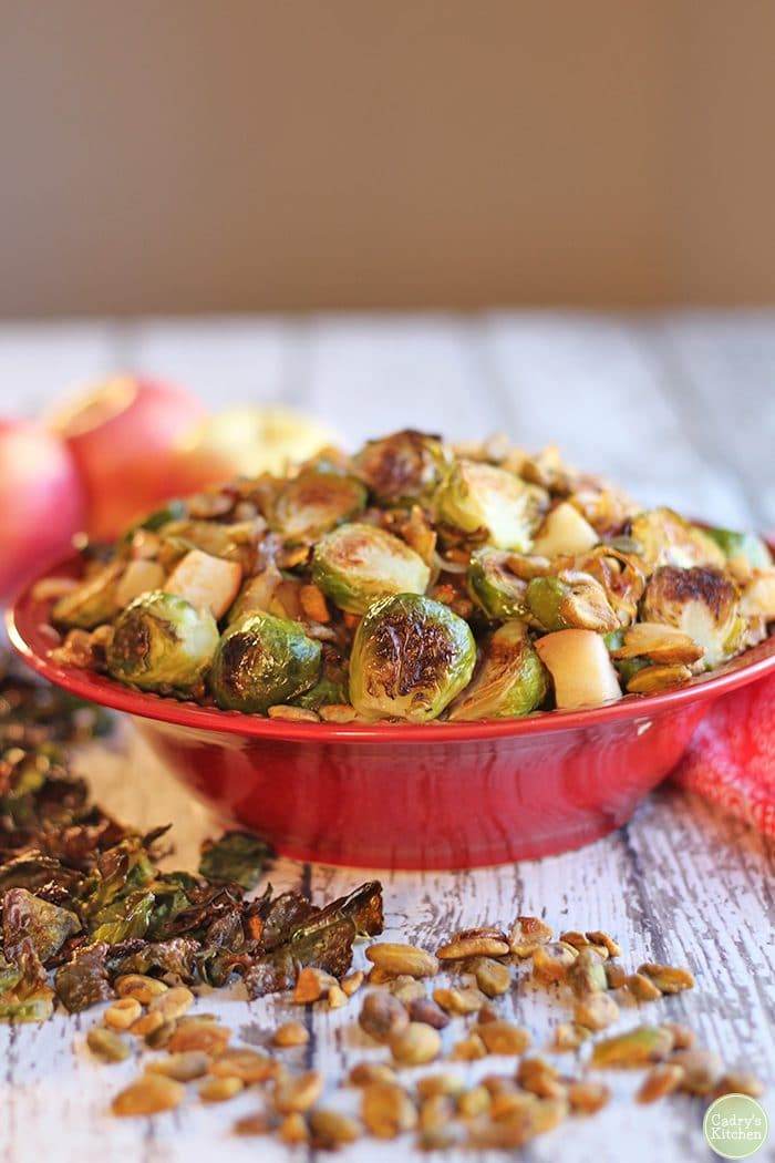 Red bowl full of roasted Brussels sprouts with apples, caramelized onions, and pistachios.