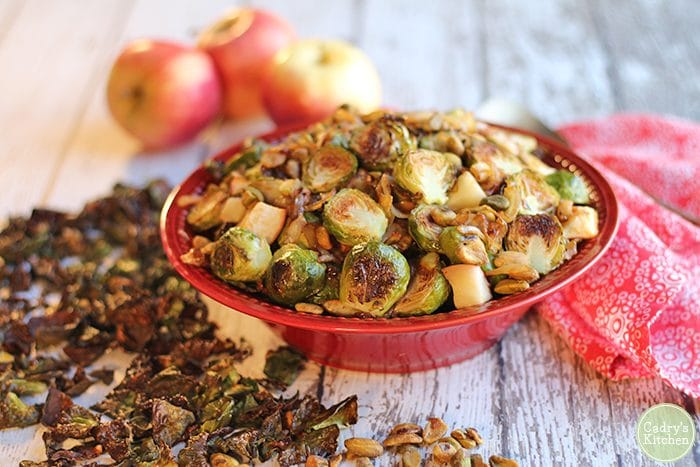 Roasted Brussels sprouts in red bowl with apples, caramelized onions, and pistachios.